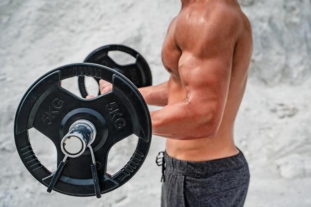 Torsoa shirtless man tillen gewichten. bodybuilding en buitensporten