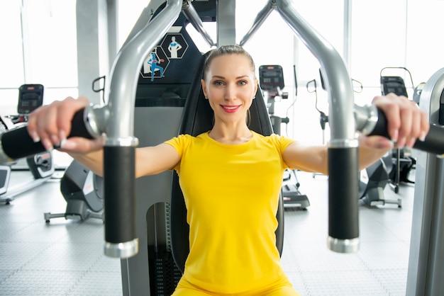 Torsoportret van vrolijke jonge volwassen kaukasische vrouw die op oefeningsmachine binnen gymnastiek uitwerken