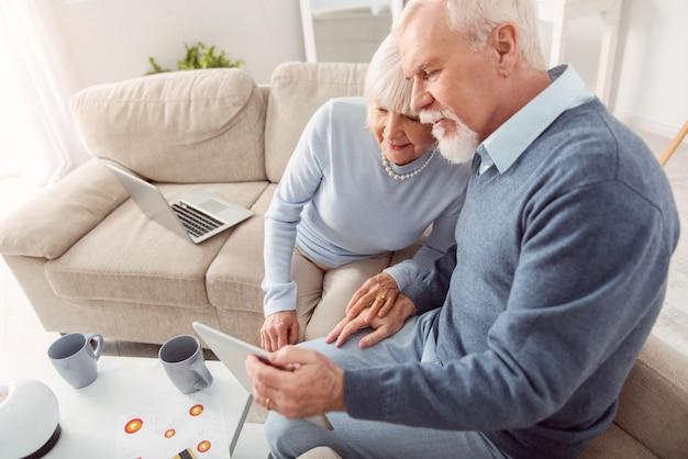 Tortelduifjes. het bovenaanzicht van een aangenaam senior koppel dat zich aan elkaar hecht terwijl ze op de bank zitten en samen een video bekijken op tablet