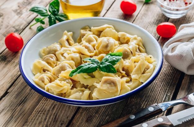 Tortellini met kaassaus, basilicumbladeren in kom op rustieke houten lijst.