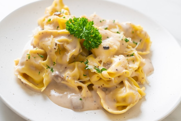 Tortellini-pasta met champignonroomsaus en kaas - italiaanse keukenstijl