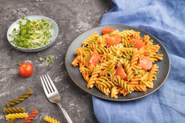 Tortiglioni griesmeel pasta met tomaat en microgreen spruiten op zwart