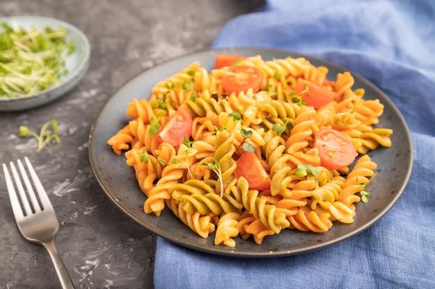 Tortiglioni griesmeel pasta met tomaat en microgroene spruiten op een zwarte betonnen ondergrond en blauw textiel