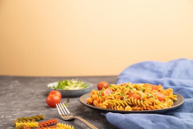 Tortiglioni griesmeel pasta met tomaat en microgroene spruiten op een zwarte en oranje achtergrond. zijaanzicht,