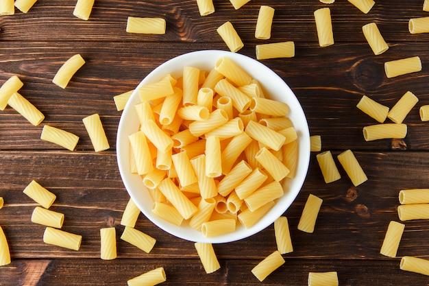 Tortiglioni pasta in een kom plat lag op een houten tafel