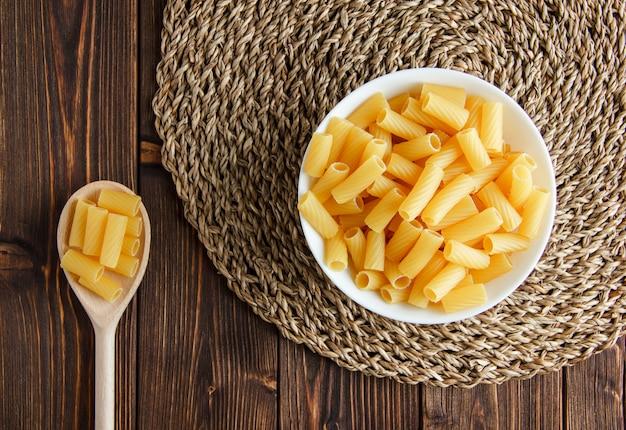 Tortiglioni pasta in kom en lepel op houten en placemat. plat lag.