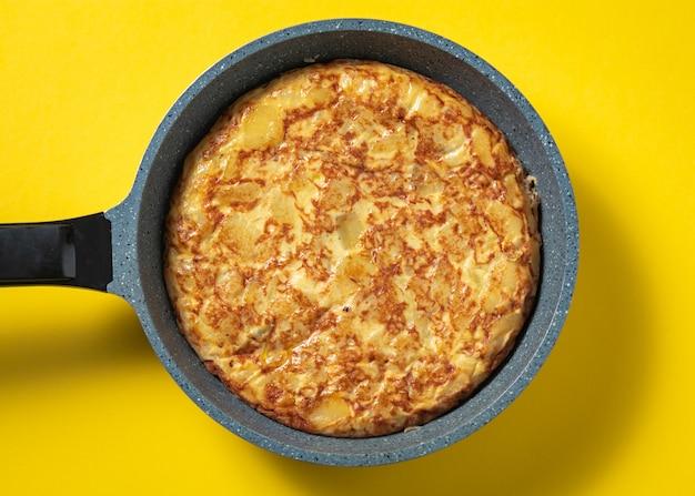 Tortilla de patatas op koekepan op gele, typische spaanse schotel.