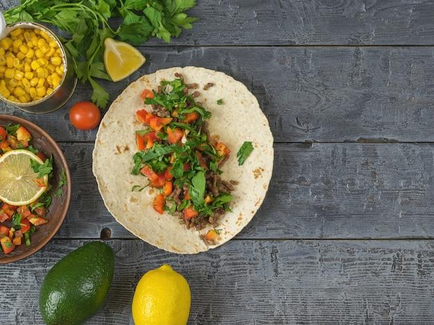 Tortilla die mexicaanse taco, vegetarische salade, citroen, peterselie, avocado en kruiden op een donkere houten lijst kookt