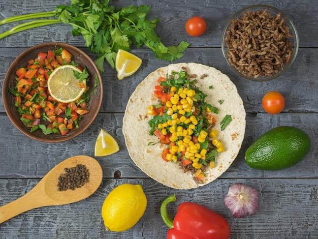 Tortilla die mexicaanse taco, vegetarische salade, peterselie, avocado en kruiden op een donkere houten lijst kookt