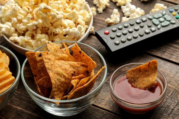 Tortilla en popcorn, tv-afstandsbediening op een bruine houten achtergrond. concept van films kijken thuis. detailopname.