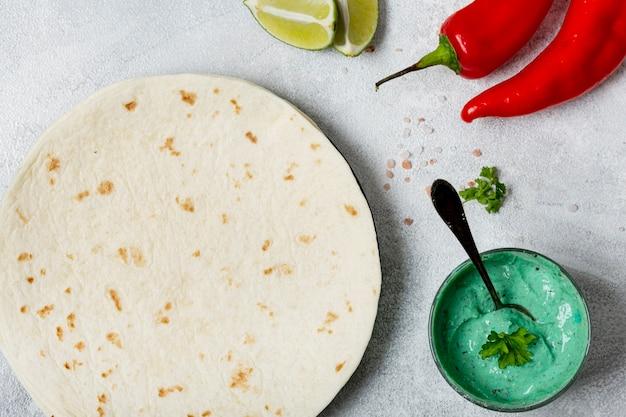 Tortilla in de buurt van biologische saus en chilipepers