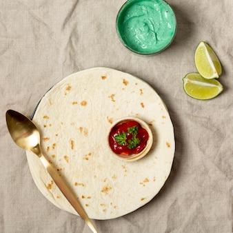 Tortilla met lepel en verschillende sauzen in de buurt van gesneden limoen