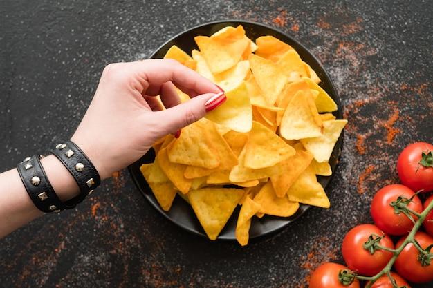 Tortilla nacho chips eten recept. vrouw hand nemen van een plakje natuurlijke gebakken chips van een bord