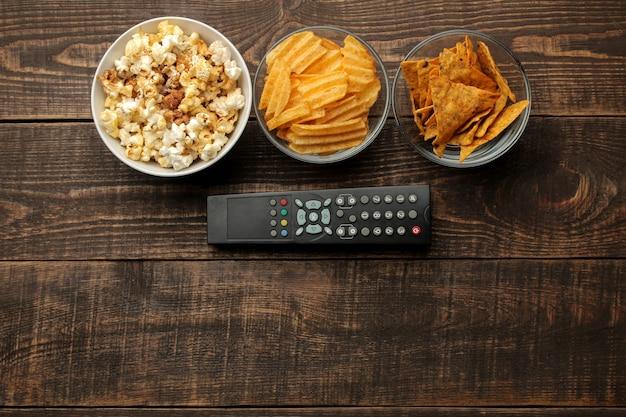 Tortilla popcorn, chips en tv-afstandsbediening op een bruine houten achtergrond. concept van films kijken thuis. uitzicht van boven
