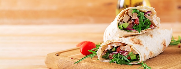 Tortilla's wraps met kip en groenten op houten achtergrond.