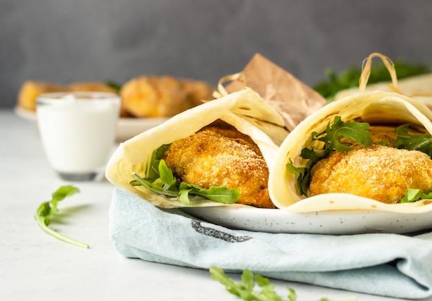 Tortilla wraps met kip of kalkoen koteletten, rucola en zure roomsaus.
