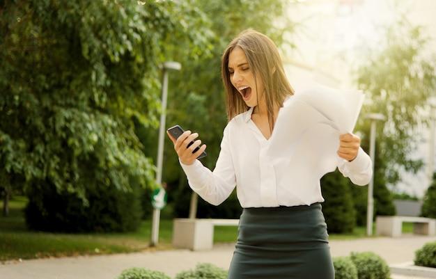 Tot hysterie gebracht, boze zakenvrouw gekleed in een witte blouse en rok