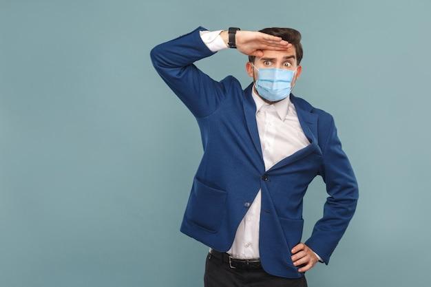 Tot nu toe met aandacht kijken jonge man met chirurgisch medisch masker serieus gezicht wegkijkend