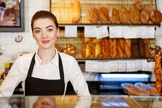 Tot uw dienst. aantrekkelijke jonge vrouw die in een bakkerij het glimlachen werkt