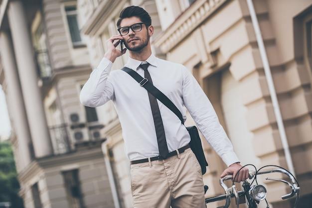 Tot ziens op kantoor! zelfverzekerde jongeman met een bril die op een mobiele telefoon praat en zijn fiets vasthoudt terwijl hij buiten staat
