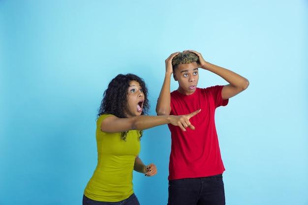 Totaal geschokt kijken naar kant als sportfans. jonge emotionele afro-amerikaanse man en vrouw in kleurrijke kleding op blauwe muur. concept van menselijke emoties, gezichtsuitdrukking, verkoop, advertentie, relaties.