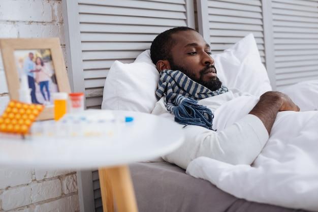 Totaal uitgeput. droevige vermoeide man met een slechte kou die zich vreselijk voelde terwijl hij thuis was in zijn warme comfortabele bed