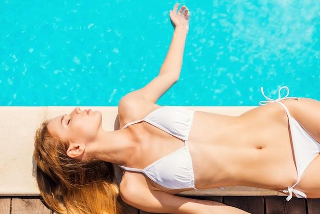 Totale ontspanning bij het zwembad. bovenaanzicht van mooie jonge vrouw in witte bikini die bij het zwembad ligt en water met de hand aanraakt