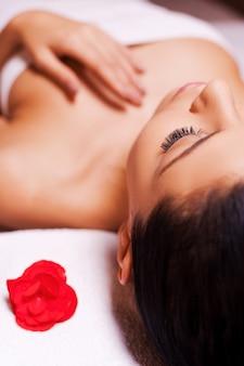 Totale ontspanning. bijgesneden afbeelding van mooie jonge vrouw gewikkeld in een handdoek liggend op een massagetafel en ogen dicht houden