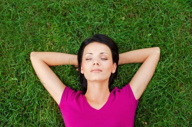 Totale ontspanning. bovenaanzicht van een mooie jonge vrouw die slaapt terwijl ze de handen achter het hoofd vasthoudt en op het groene gras ligt