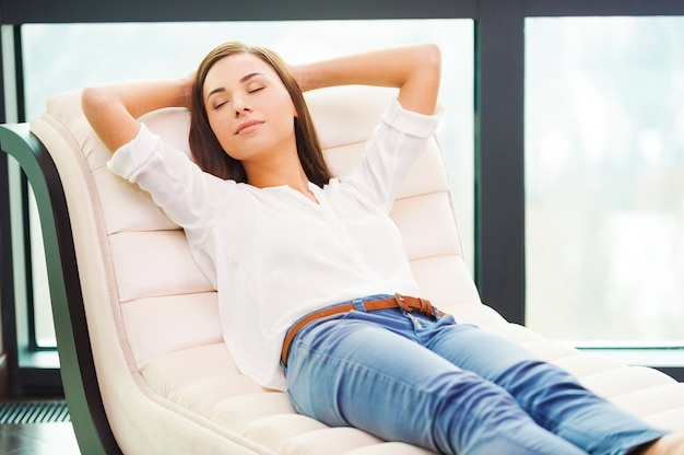 Totale ontspanning. mooie jonge vrouw hand in hand achter haar hoofd terwijl ze op de bank slaapt