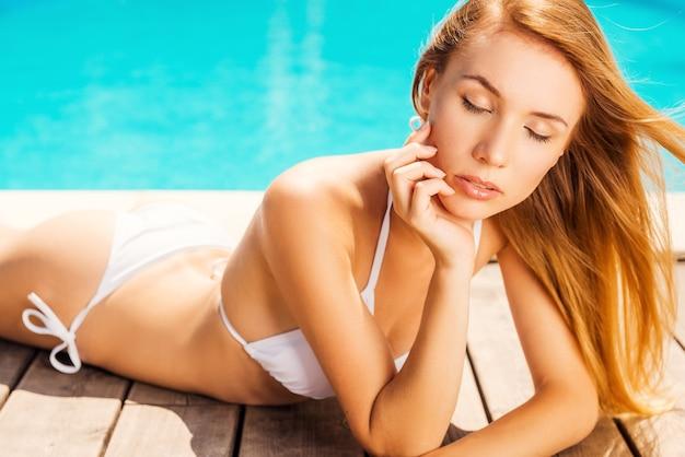 Totale ontspanning. mooie jonge vrouw in witte bikini die de hand op de kin houdt en de ogen gesloten houdt terwijl ze bij het zwembad ligt