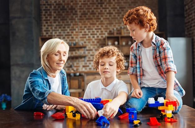 Totale rust en begrip. vrolijke oudere dame die een plastic stuk speelgoed blok neemt terwijl ze naast haar mannelijke kleinkinderen zit en met hen praat