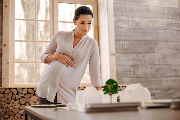 Totale tevredenheid. nadenkend doordachte zwangere ontwerper buik omarmen terwijl naar beneden te kijken en leunend op tafel