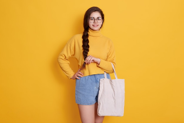 Tote bag in handen van schattig tienermeisje met vlecht en bril, trui en spijkerbroek korte, poseren geïsoleerd over gele muur