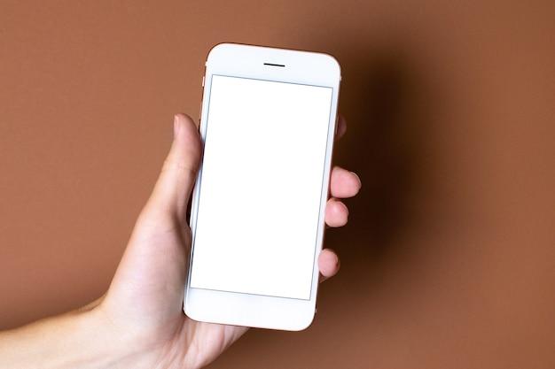 Touch screen mobiele telefoon in de hand op bruin oranje achtergrond.