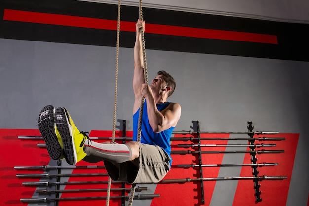 Touw beklim de oefening van de oefeningsmens bij gymnastiek
