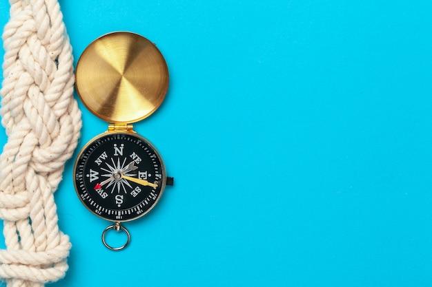 Touw met kompas op blauwe tafel