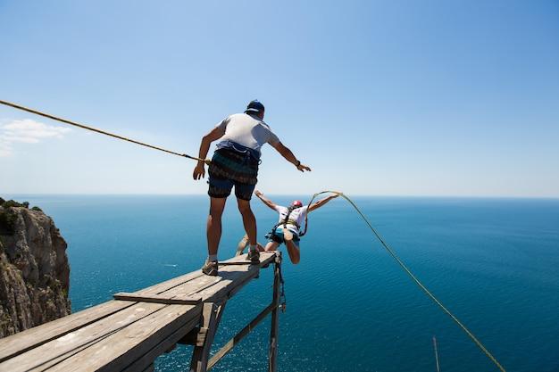 Touw springen van een klif met een touw in het water. de oceaan. zee. berg.