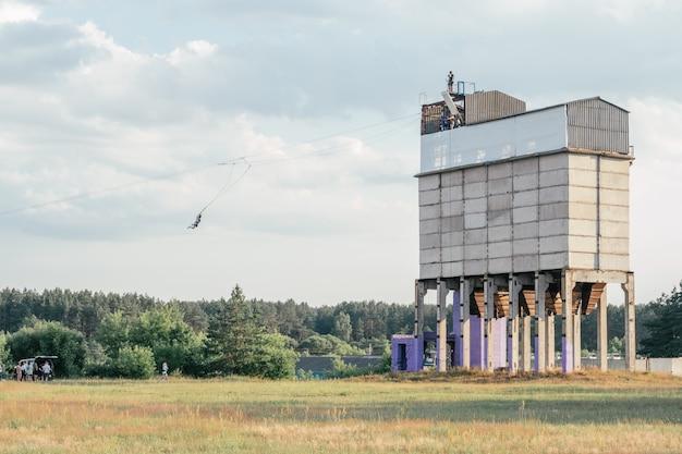 Touw springen van hoge oude verlaten graanschuur gebouw, extreme sport