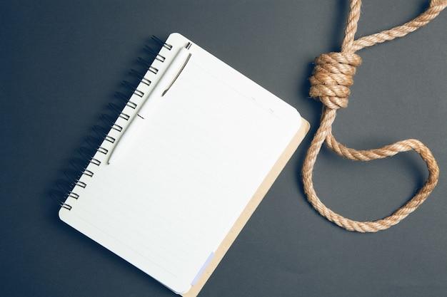 Touw voor de galg en een notitieboekje op een zwarte achtergrond. zelfmoordbrief concept