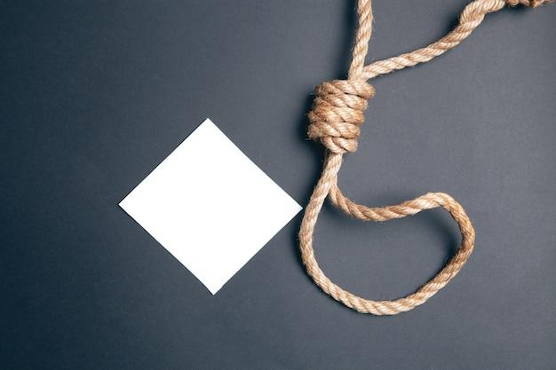 Touw voor de galg en papier op een zwarte achtergrond. zelfmoordbrief concept