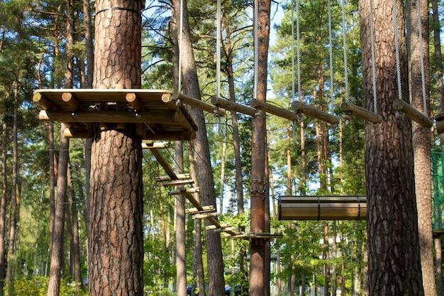 Touwpark in het dennenbos op de zomerdag