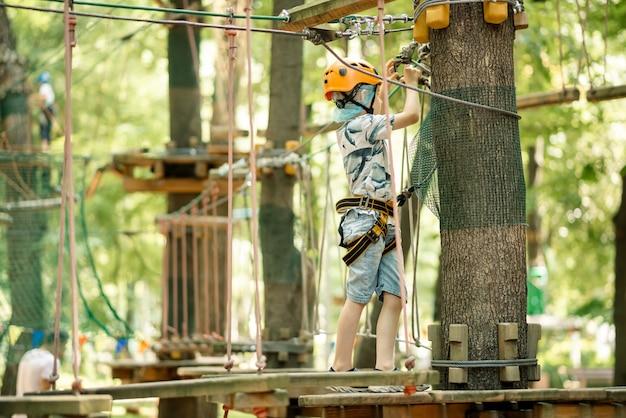 Touwpark voor kinderen. een jonge jongen in een flap klimt op obstakels. actieve sportrecreatie van het kind.