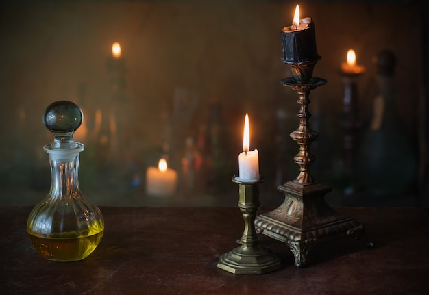 Toverdrank, oude boeken en kaarsen op donker