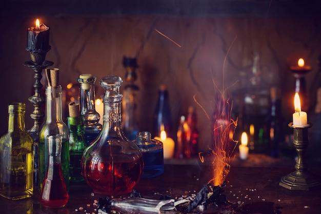 Toverdrank, oude boeken en kaarsen op donkere achtergrond