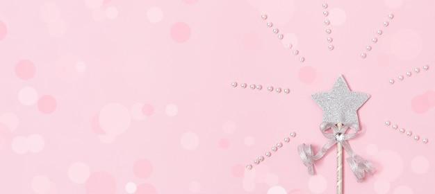 Toverstaf, heldere zilveren ster met glans geïsoleerd op roze