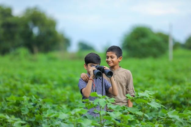 Tow kleine indiase jongen geniet in de natuur met een verrekijker