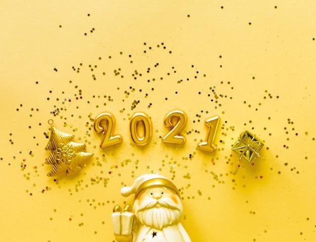 Toy santa claus met een geschenkdoos in gouden kleur en de inscriptie 2021 op een gele achtergrond vakantieconcept, bovenaanzicht, kopieer ruimte.