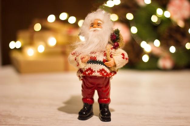 Toy santa claus op de achtergrond van geschenkdozen en een kerstkrans met een lichtgevende slinger.