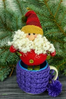 Toy santa claus op ski's op de achtergrond van dennentakken en mokken.